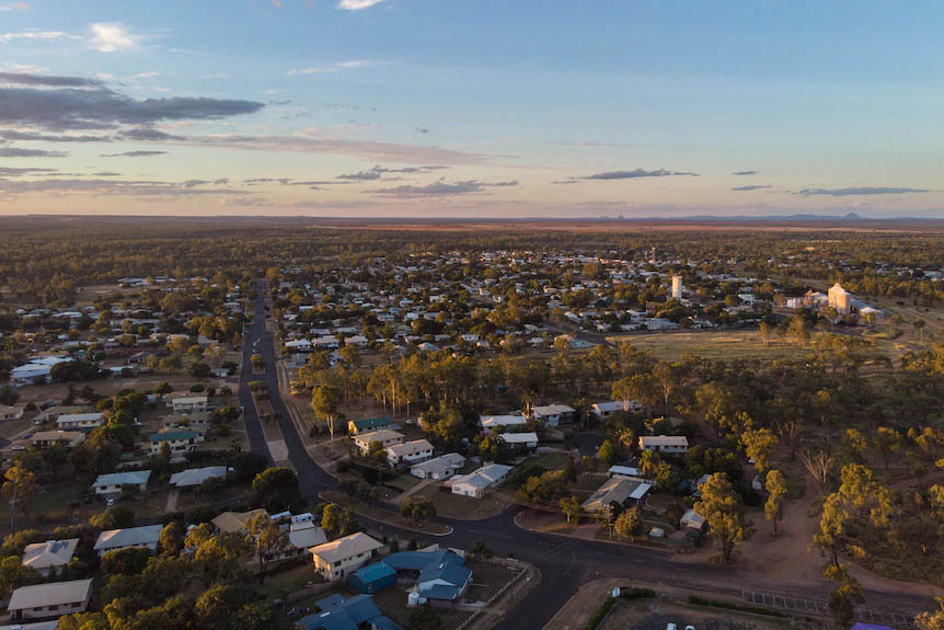A drone shot of Clermont at sunset, a small regional town, white silos and mountains in distance.